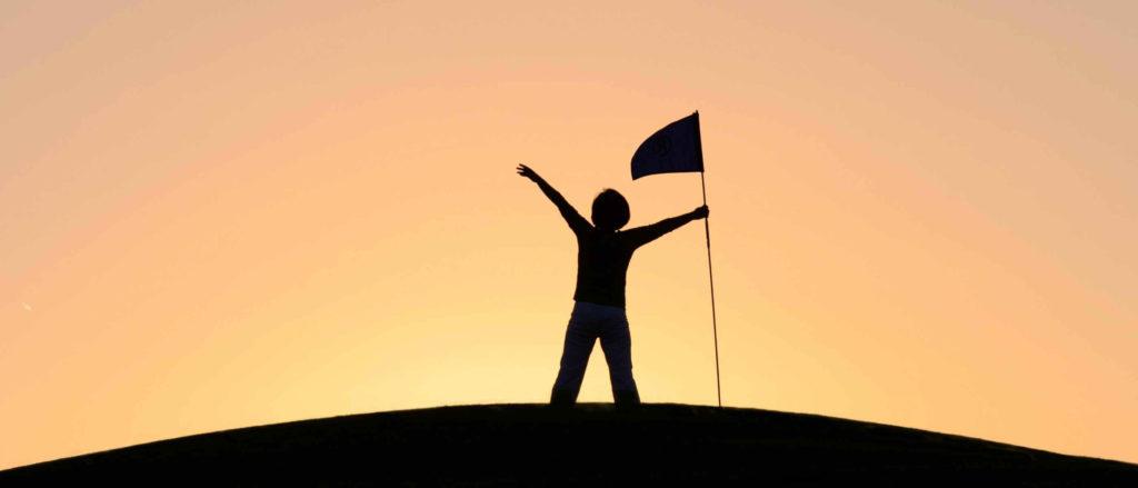 człowiek na górze z flagą - zwycięstwo
